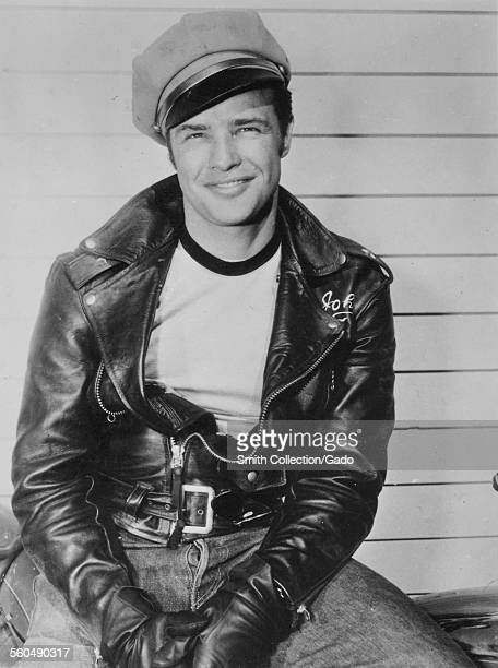 Actor Marlon Brando wearing a leather jacket jeans and a conductor hat 1954