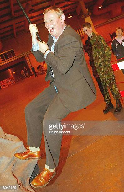 Actor Martin Clunes climbs an artificial climbing wall at the Prince's Trust xl Celebration Day on March 4 2004 in Wembley London The event...