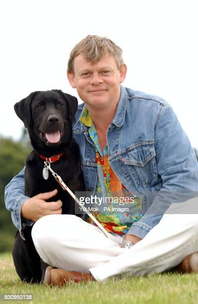Actor Martin Clunes the voice of the television cartoon character dog 'Merlin' with an eightmonth old guide dog also named Merlin who is being...