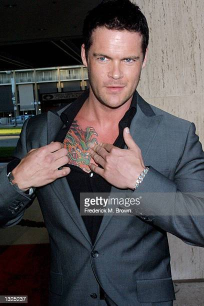 Actor Matt Schulze displays his tattoo while arriving at the screening of the motion picture 'Kiss Of The Dragon' June 25 2001 in Los Angeles CA The...