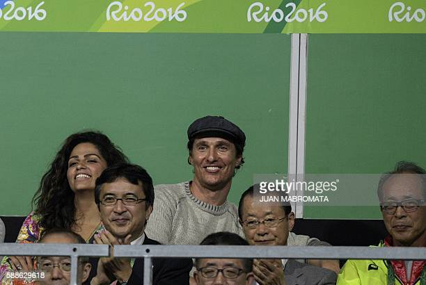 US actor Matthew McConaughey and his wife Camila Alves watch the men's singles bronze medal table tennis match between Japan's Jun Mizutani and...