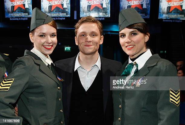 Actor Matthias Schweighoefer stands between Russian dressed hostesses during the 'Russendisko' World Premiere at CineStar on March 21 2012 in Berlin...