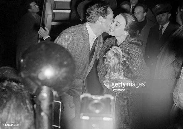 Actor Mel Ferrer kisses his wife actress Audrey Hepburn upon his arrival from Paris Miss Hepburn carries pet dog Famous during the Ciampino reunion...