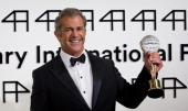 Actor Mel Gibson poses with the Crystal Globe for Outstanding Artistic Contribution to World Cinema at the opening ceremony of the 49th Karlovy Vary...