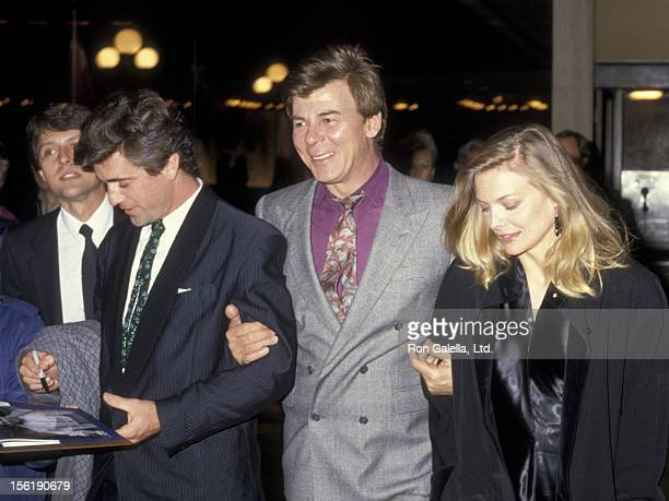 Actor Mel Gibson talent agent Ed Limato and actress Michelle Pfeiffer attend the premiere of 'Out Of Africa' on December 10 1985 at the Plitt Theater...