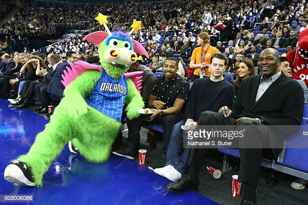 Actor Michael B Jordan manager Kenny Goodman and NBA Legend Hakeem Olajuwon takes in the game with the mascot Stuff of the Orlando Magic against the...