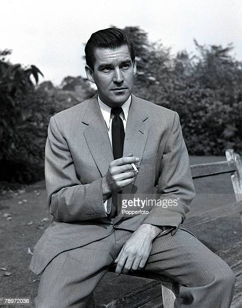 Actor Michael Craig smoking a cigarette as he sits on a bench outside Pinewood Studios 1956