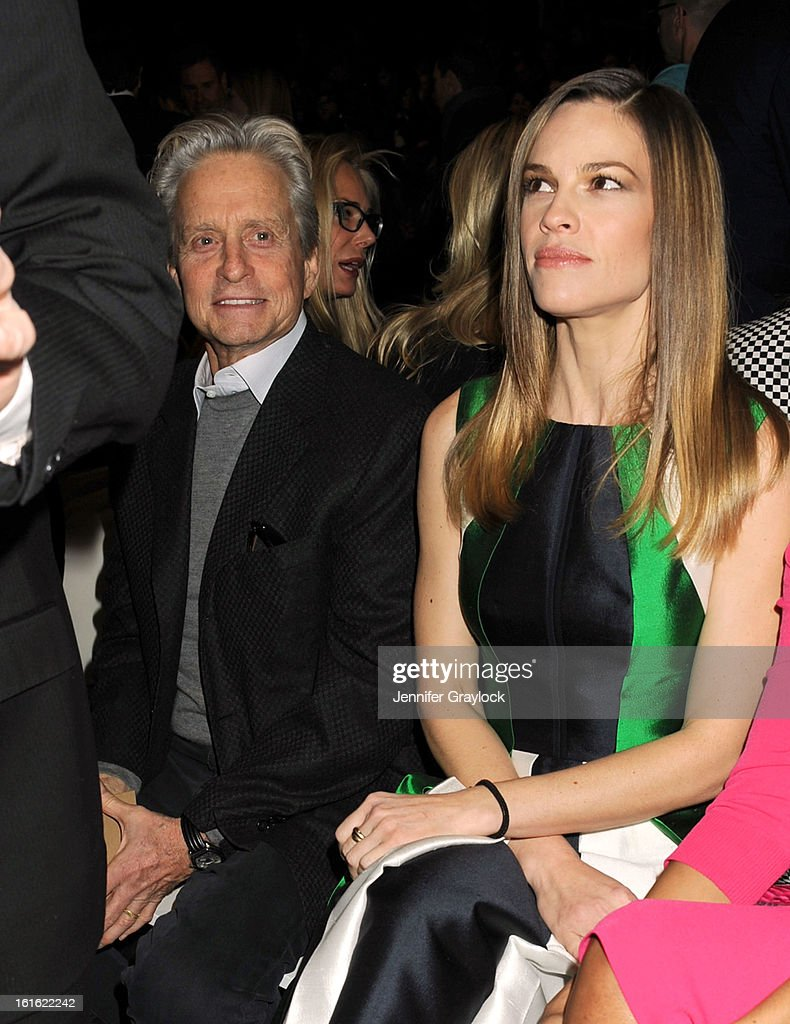 Actor Michael Douglas and Actress Hilary Swank front row during the Michael Kors Fall 2013 Mercedes-Benz Fashion Show at The Theater at Lincoln Center on February 13, 2013 in New York City.