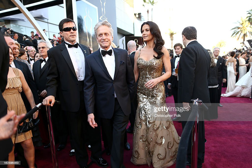 Actor <a gi-track='captionPersonalityLinkClicked' href=/galleries/search?phrase=Michael+Douglas&family=editorial&specificpeople=171111 ng-click='$event.stopPropagation()'>Michael Douglas</a> (L) and his wife actress Catherine Zeta-Jones arrive at the Oscars held at Hollywood & Highland Center on February 24, 2013 in Hollywood, California.