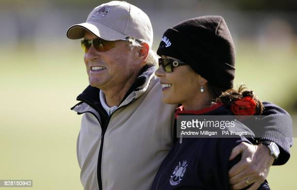 Actor Michael Douglas and wife Catherine Zeta Jones keep warm during a practice round on the Old Course at St Andrews Fife Tuesday September 27 2005...