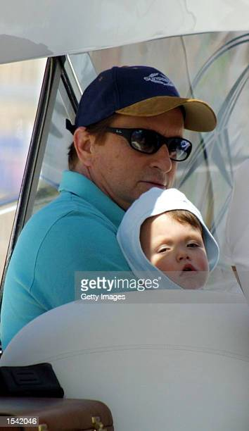 Actor Michael Douglas holds his son Dillon aboard the Sunseeker May 14 2002 in Monte Carlo Monaco America's Cup skippers and celebrities from the...