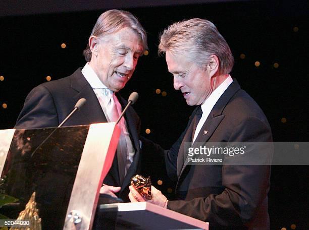 Actor Michael Douglas presents the 2005 Golden Kinnaree Awards to director Joel Schumacher at the Bangkok International Film Festival at the Queen...