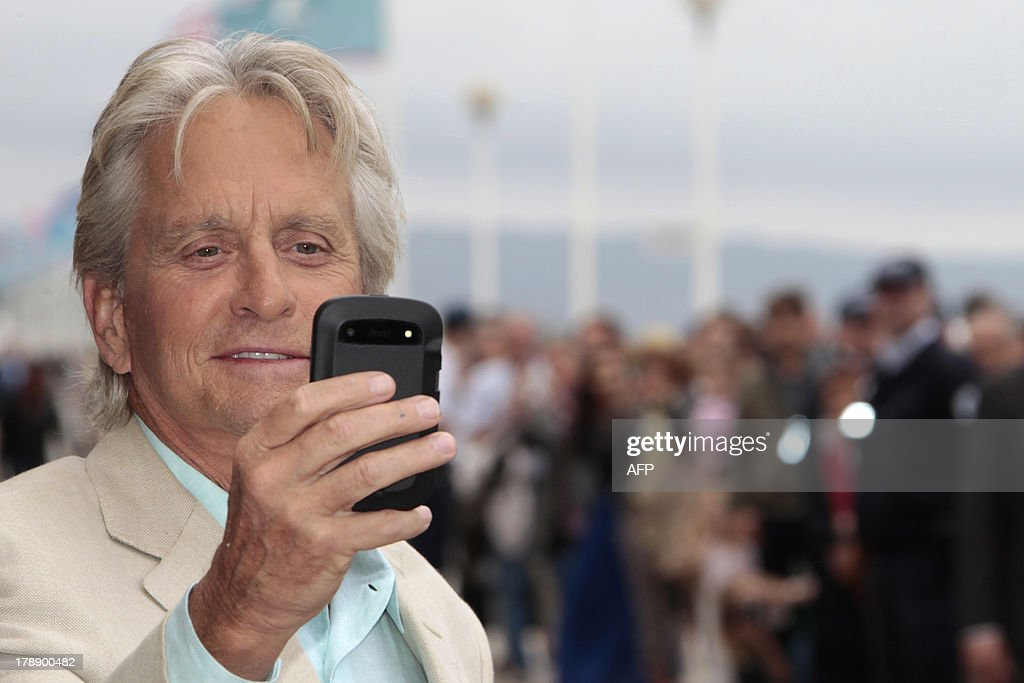 US actor Michael Douglas takes a picture on his smart phone as he unveils the beach locker room dedicated to him on the Promenade des Planches on August 31, 2013 in the French northwestern sea resort of Deauville, as part of the Deauville US Film Festival.