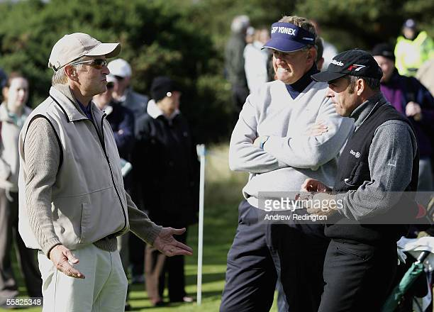 Actor Michael Douglas talks with Colin Montgomerie of Scotland and Paul McGinley of Ireland during the first round of the Dunhill Links Championships...