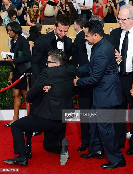 Actor Michael Pena tries to help actor Bradley Cooper remove Ukrainian reporter and prankster Vitalii Sediuk from Cooper's legs on the red carpet at...