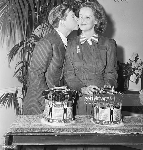 Actor Mickey Rooney plants a kiss on the cheek of actress Bette Davis after they were crowned the King and Queen of the Movies in a nationwide poll...