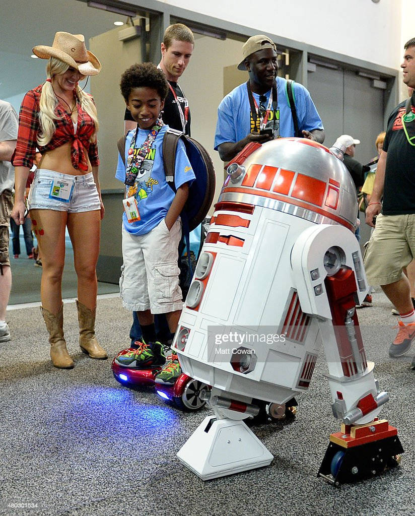 Actor Miles Brown looks at an R2D2 character from the 'Star Wars' movie franchise during ComicCon International 2015 on July 10 2015 in San Diego...