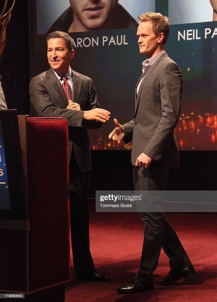 Actor Neil Patrick Harris (R) walks onstage to join Academy of Television Arts & Sciences Chairman & CEO Bruce Rosenblum during the 65th Primetime Emmy Awards nominations at the Television Academy's Leonard H. Goldenson Theatre on July 18, 2013 in North Hollywood, California.