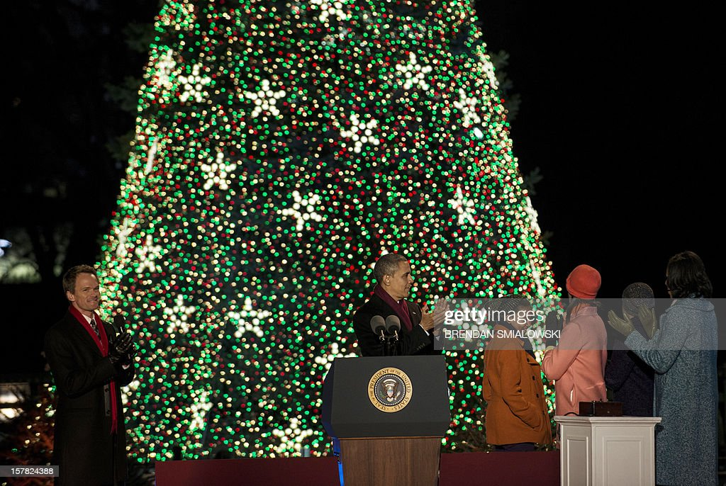 Actor Neil Patrick Harris (L) watches as US President Barack Obama, US First Lady Michelle Obama and their children Sasha and Malia illuminate the National Christmas Tree during the 90th annual lighting on the Ellipse of the National Mall December 6, 2012 in Washington, DC. Obama and others attended the event which included entertainment before the lighting of the National Christmas Tree. AFP PHOTO/Brendan SMIALOWSKI