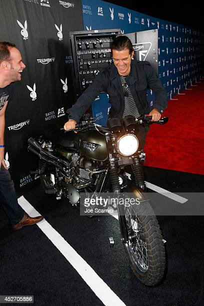 Actor Orlando Bloom wins a donation to the charity of his choice after successfully starting the Triumph Scrambler Custom on display at the Playboy...