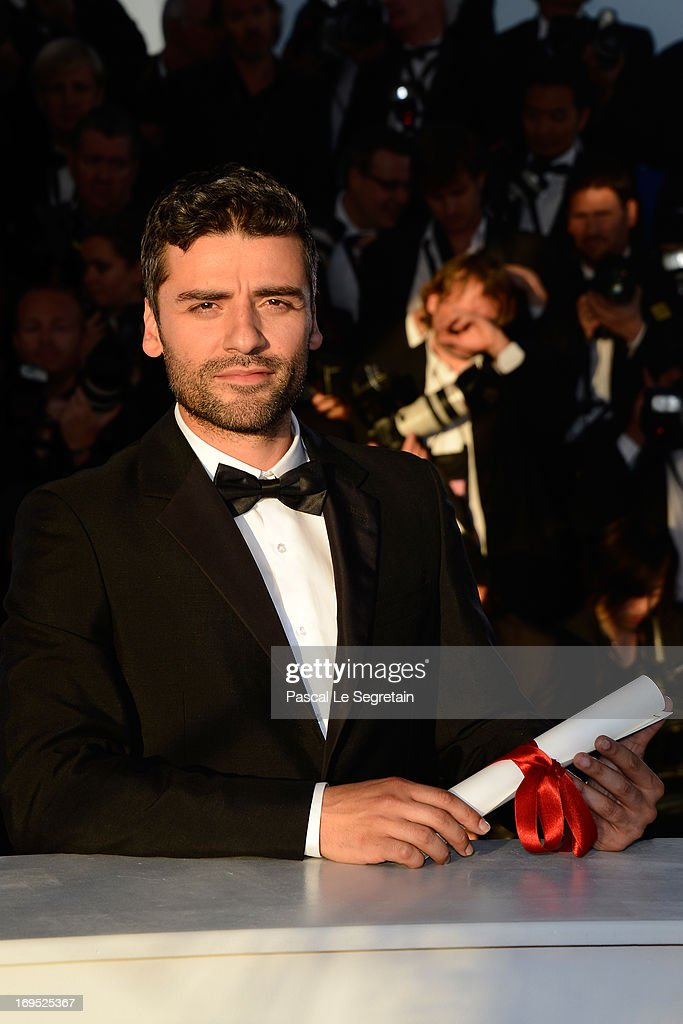 Actor <a gi-track='captionPersonalityLinkClicked' href=/galleries/search?phrase=Oscar+Isaac&family=editorial&specificpeople=2275888 ng-click='$event.stopPropagation()'>Oscar Isaac</a> poses on behalf of directors Joel and Ethan Coen after they were awarded with the Grand Prix for the film 'Inside Llewyn Davis' at the Palme D'Or Winners Photocall during the 66th Annual Cannes Film Festival at the Palais des Festivals on May 26, 2013 in Cannes, France.