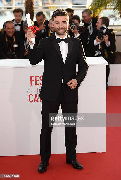 Actor Oscar Isaac poses on behalf of directors Joel and Ethan Coen after they were awarded with the Grand Prix for the film 'Inside Llewyn Davis' at...