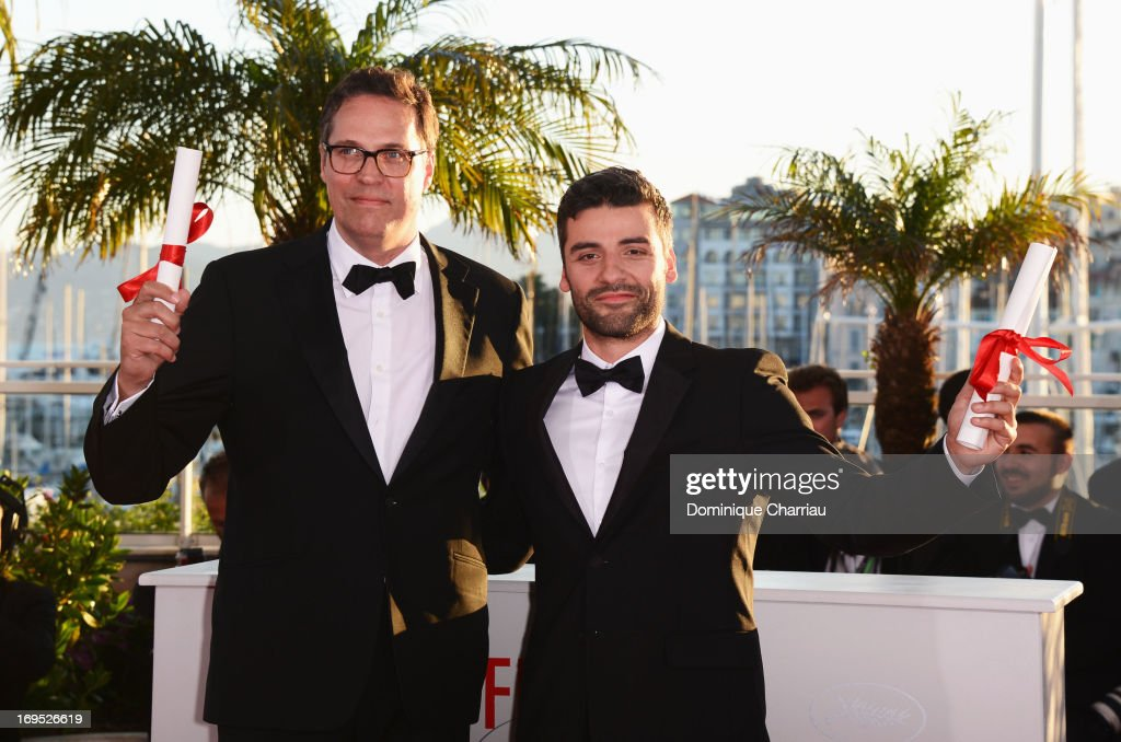 Actor Oscar Isaac (R) poses on behalf of directors Joel and Ethan Coen after they were awarded with the Grand Prix for the film 'Inside Llewyn Davis' at the photocall for award winners during the 66th Annual Cannes Film Festival at Palais des Festivals on May 26, 2013 in Cannes, France.