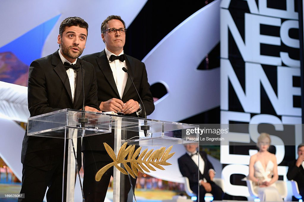 Actor Oscar Isaac (L) speaks on stage after he received for directors Joel and Ethan Coen the Grand Prix award for 'Inside Llewyn Davis' on stage during the Closing Ceremony of the 66th Annual Cannes Film Festival at the Palais des Festivals on May 26, 2013 in Cannes, France.