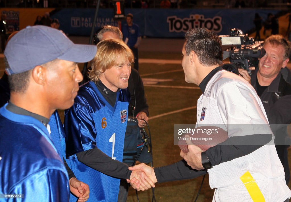 Actor Owen Wilson of Team Liberty shakes hands with former NFL player Kurt Warner of Team Freedom during the Got Your 6 And Pat Tillman Foundation benefit game on December 13, 2012 in Norwalk, California.