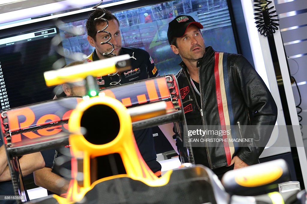 US actor Patrick Dempsey (R) looks on in the Infiniti Red Bull Racing's pit at the Monaco street circuit, on May 29, 2016 in Monaco, ahead of the Monaco Formula 1 Grand Prix. / AFP / JEAN