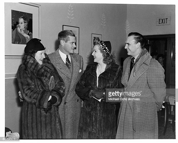 Actor Paul Kelly and his wife playwright Dorothy Mackaye talk with actress Betty Grable and her husband actor Jackie Coogan before an event in Los...