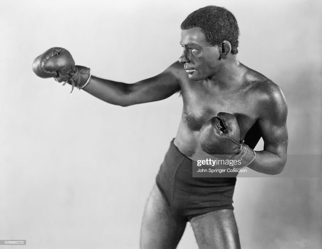 Actor Paul Muni wears body makeup to play the role of boxer Joe Gans in the 1929 film Seven Faces