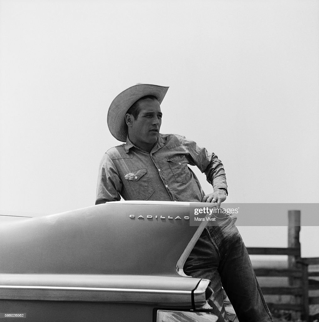 Actor Paul Newman leans on the trunk of a Cadillac on the set of the film Hud. Near Claude, Texas, USA. | Location: near Claude, Texas, USA.
