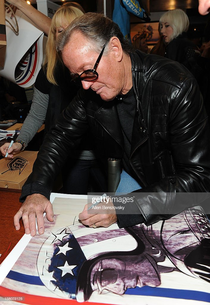 Actor Peter Fonda signs autographs at the launch of his new men's fashion line and protective riding gear collection for Troy Lee Designs at Troy Lee Boutique & Design Center on December 8, 2012 in Laguna Beach, California.