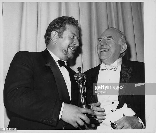 Actor Peter Ustinov holding the Academy Award for Best Supporting Actress which he accepted on behalf of Margaret Rutherford He is with the Ed Begley...