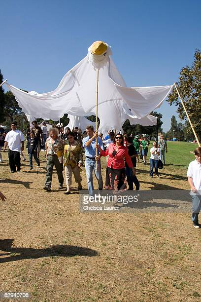 Actor Pierce Brosnan and his wife Keeley Shaye Smith join a procession carrying giant banners representing doves of peace during Roots Shoots Day of...