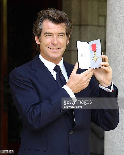 Actor Pierce Brosnan poses with his honorary OBE in recognition of his outstanding contribution to drama and the British Film Industry presented by...