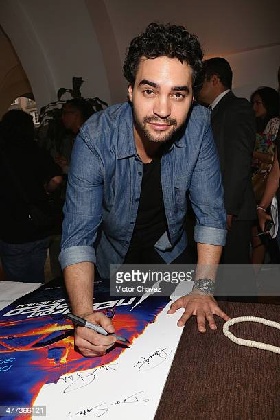Actor Ramon Rodriguez signs a poster during a press junket and photocall to promote his new film 'Need For Speed' at Four Seasons Hotel on March 8...
