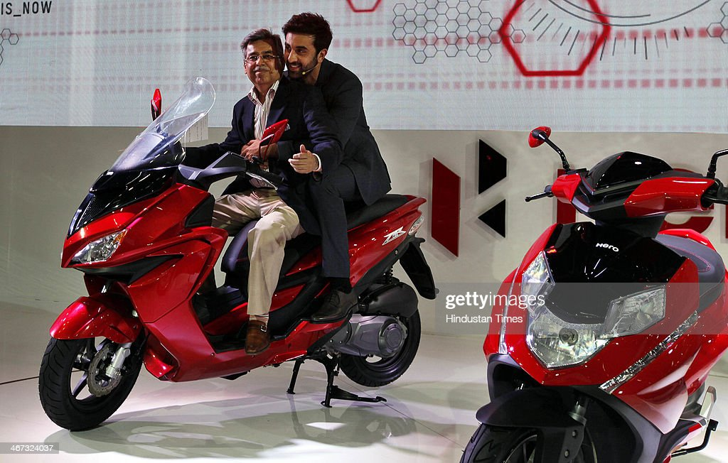 Actor Ranbir Kapoor takes a back seat with Pawan Munjal, the Managing Director and CEO of Hero MotoCorp during the launch of two powerful and sleek looking scooters - the 150cc ZIR range, and the aggressively styled 125cc Dare at Hero Pavilion during the 12th Auto-Expo 2014 at India Expo Mart on February 6, 2014 in Greater Noida, India.