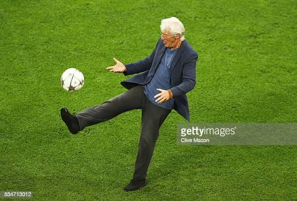 Actor Richard Gere kicks the ball on the San Siro pitch after a Real Madrid training session on the eve of the UEFA Champions League Final against...