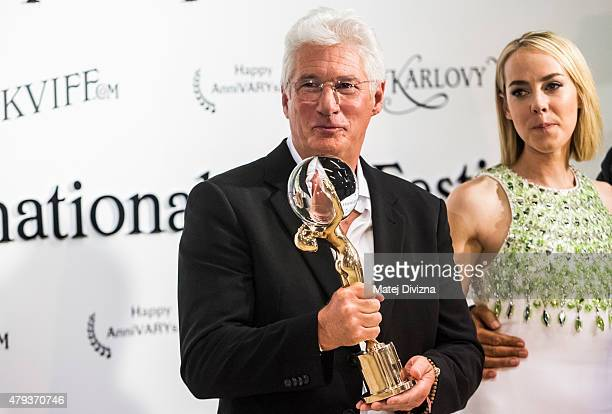 Actor Richard Gere poses with the Crystal Globe for Outstanding Artistic Contribution to World Cinema and actress Jena Malone at the opening ceremony...