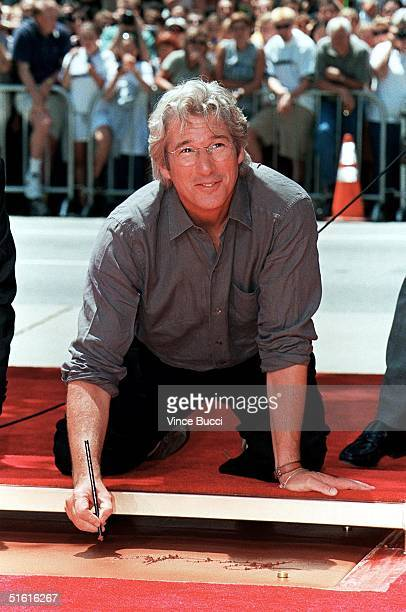 US actor Richard Gere signs his name before placing his hands and feet in cement during a ceremony 26 July 1999 at Mann's Chinese Theatre in...