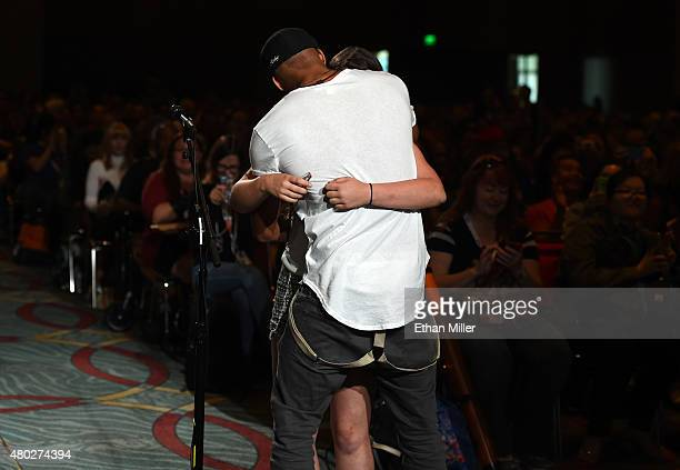 Actor Ricky Whittle embraces fan Kayla Vlcek as she asks a question at a special video presentation and panel for 'The 100' during ComicCon...