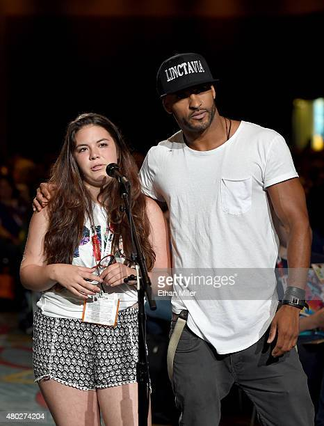 Actor Ricky Whittle visits with fan Kayla Vlcek as she asks a question at a special video presentation and panel for 'The 100' during ComicCon...