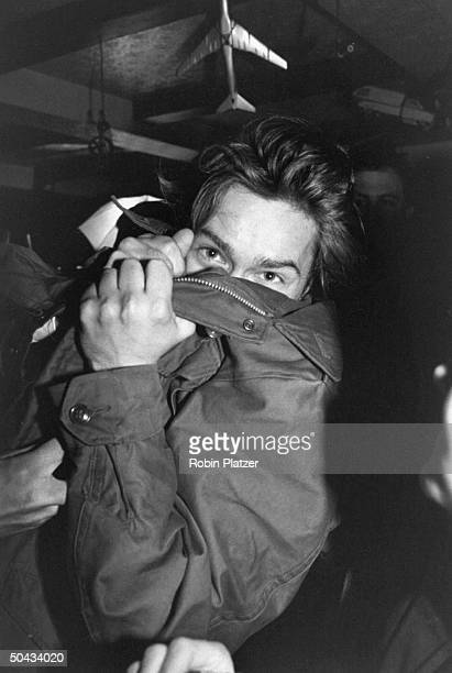 Actor River Phoenix covering his face w his coat at an Artists Against Fur event