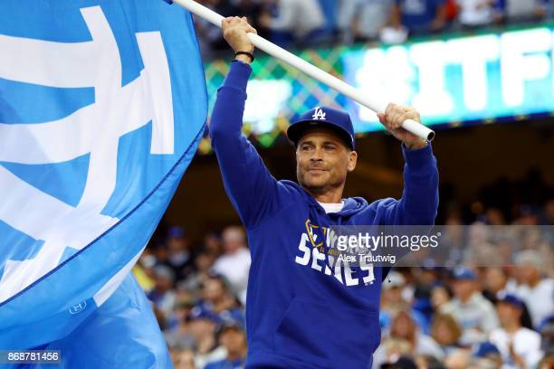 Actor Rob Lowe waves a Dodgers flag on the dugout prior to Game 6 of the 2017 World Series between the Houston Astros and the Los Angeles Dodgers at...
