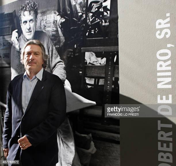 US actor Robert De Niro poses in front of a poster announcing his late father Robert De Niro Senior painting exhibition 18 June 2005 in 'La piscine'...