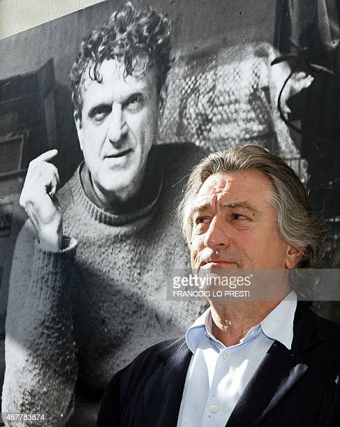 US actor Robert De Niro poses in front of a poster announcing his late father Robert De Niro Senior painting exhibition 18 June 2005 in 'La piscine'...