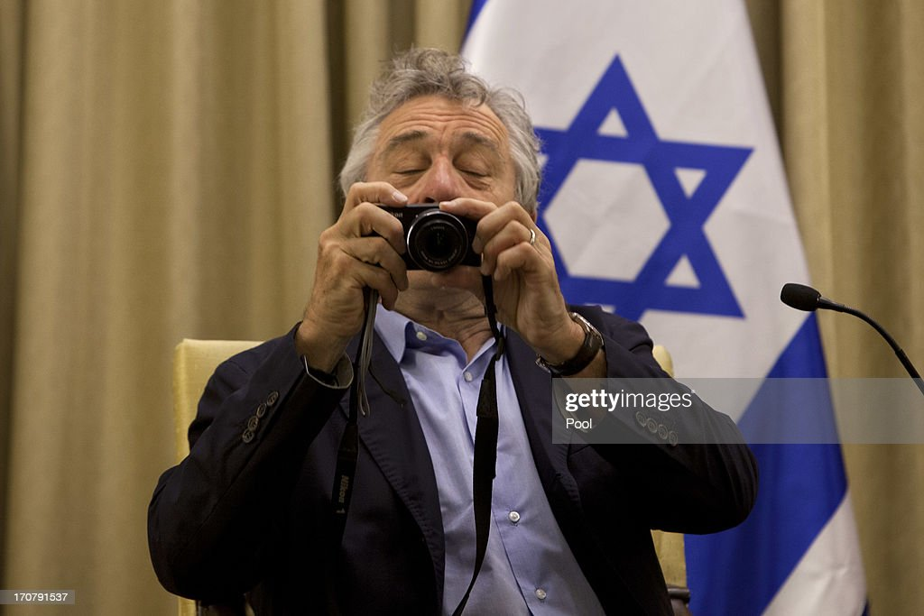 Actor <a gi-track='captionPersonalityLinkClicked' href=/galleries/search?phrase=Robert+De+Niro&family=editorial&specificpeople=201673 ng-click='$event.stopPropagation()'>Robert De Niro</a> takes a photo of members of the media prior to his meeting with Israel's President Shimon Peres, at the President's residence in Jerusalem on June 18, 2013 in Jerusalem, Israel.