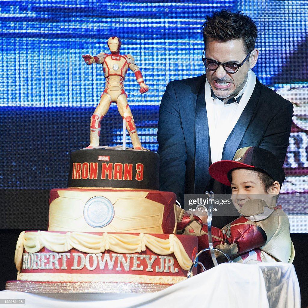 Actor Robert Downey Jr. cuts his 48th birthday cake with a fan during the 'Iron Man 3' South Korea Premiere at Times Square on April 4, 2013 in Seoul, South Korea. Robert Downey Jr. is visiting South Korea to promote his recent film 'Iron Man 3' which will be released on April 25 in South Korea.